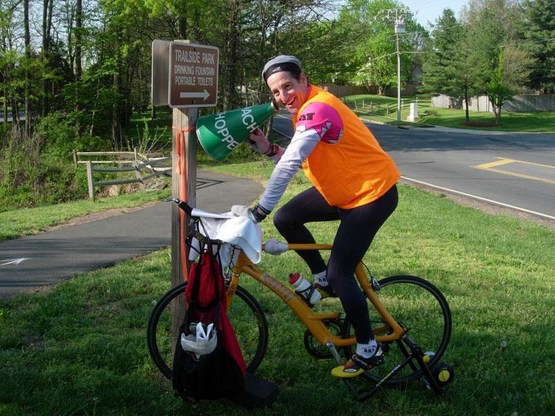 Triathlon   Trial Lawyer Doug Landau pedalling, reading and volunteering at the run turnaround.   Talk about