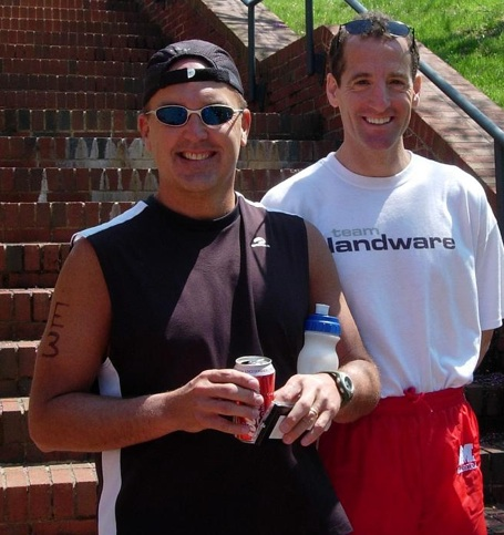 Doug   Landau shown with prize winner Tom Cook. Cook, a devastatingly fast runner,  makes the Triathlon Trial Lawyer look like a snail ! Cook is the Race Director  for the June Tim Harmon 5km race at the Fairfax Government Center and also works at Potomac River Running, Reston Town Center, on weekends.